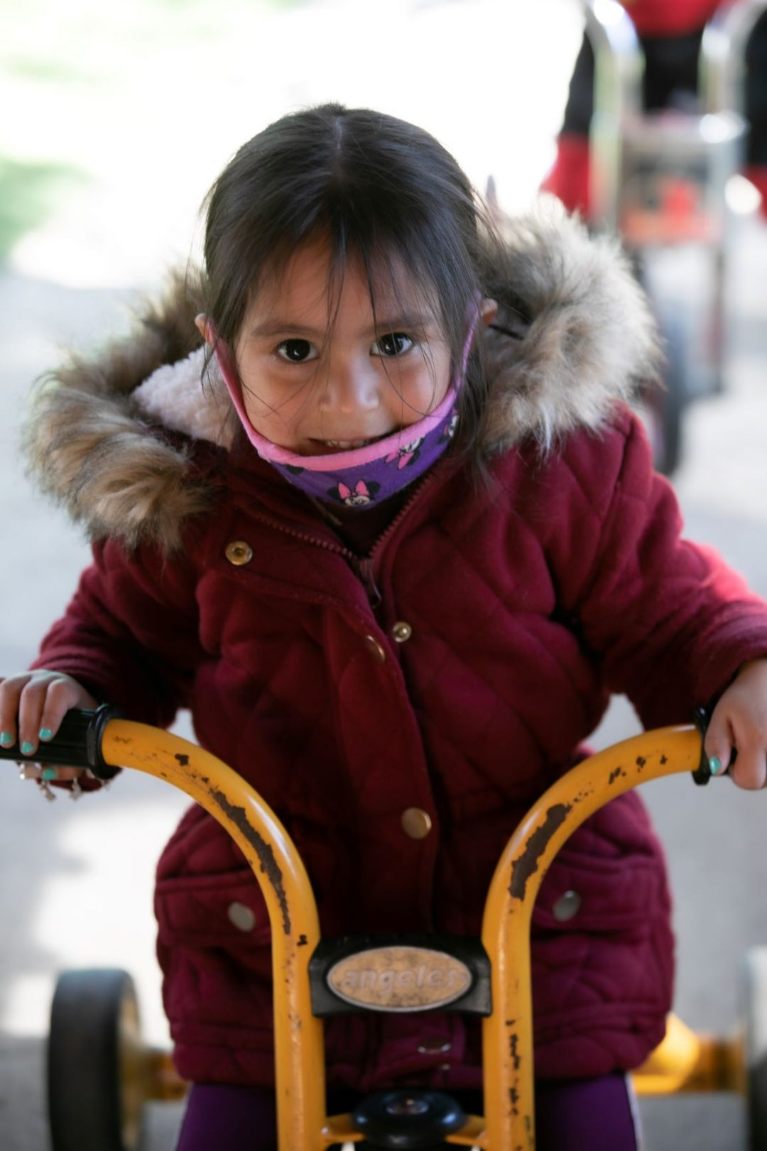 Girl in a red coat riding a tricycle