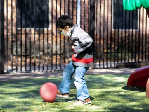 Boy kicking a ball outside