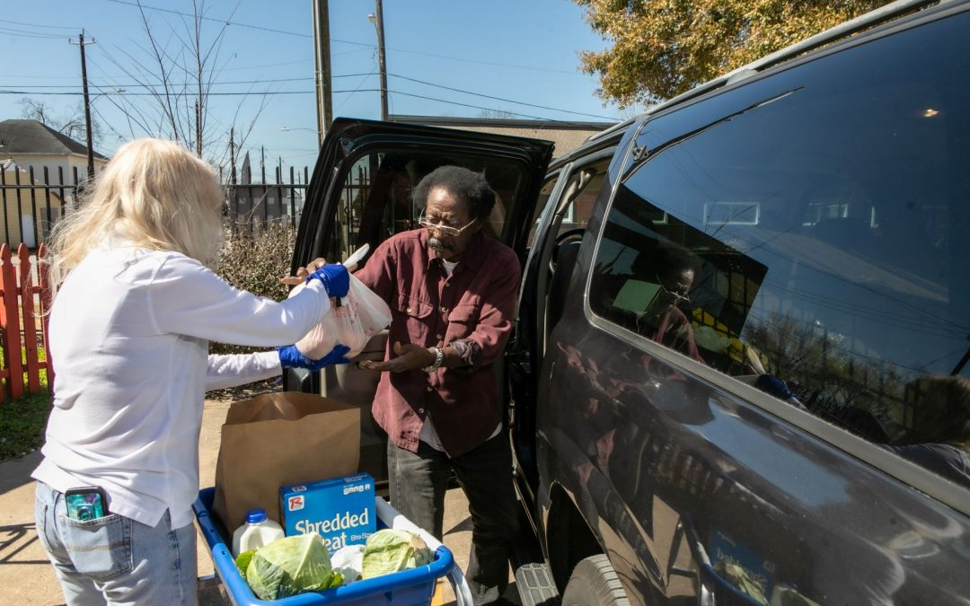 Volunteer Handing Groceries to a client at Food Pantry