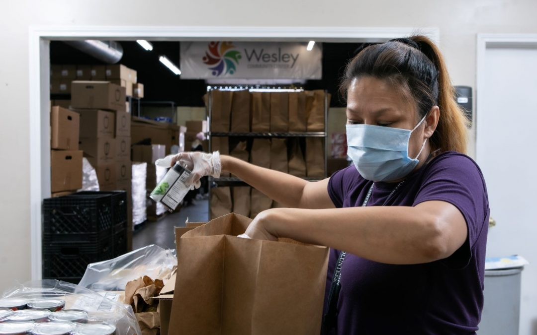Woman Packing a Bag of Groceries at the Food Pantry